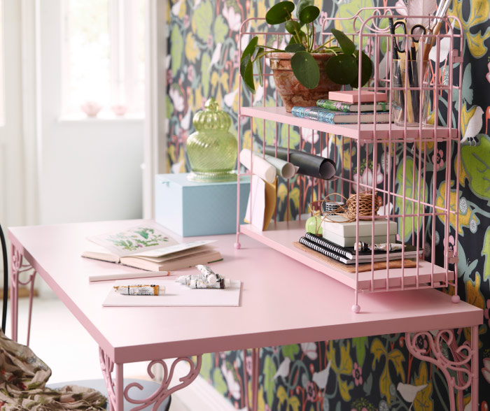 A pink desk and add-on unit with traditional ornaments.