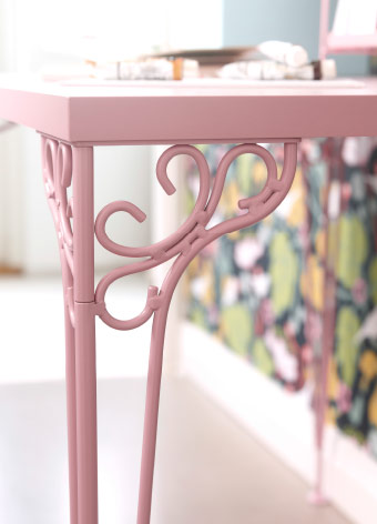 Close-up of a pink desk leg with ornaments.