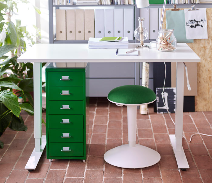 A home office with a white sit and stand desk, a green chest of drawers and a white standing support with a green seat cushion.