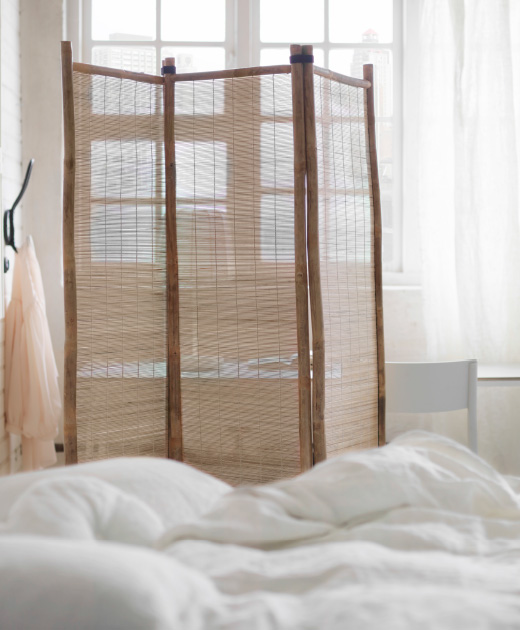 A room divider made of bamboo, shown in a bedroom.