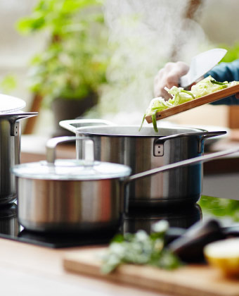 One stainless steel saucepan with glass lid and one pot, shown on a hob.