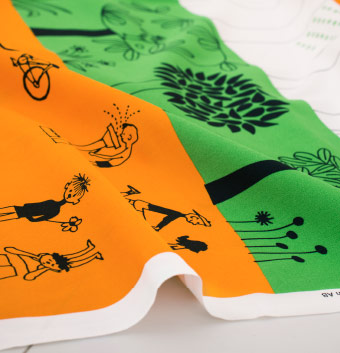 A close-up of a metre fabric in white, green and orange with a fun pattern of playing children.