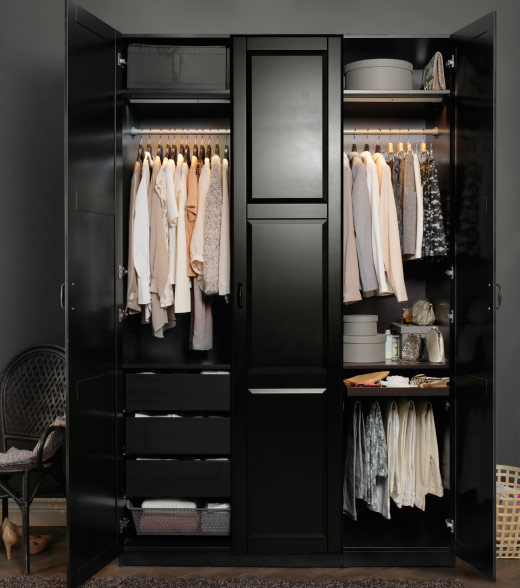 A black-brown wardrobe filled with clothes in light pastel colours