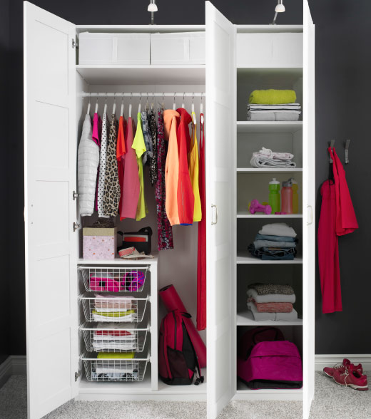 A white wardrobe filled with clothes in bright colours