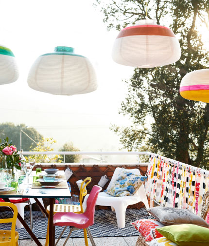 View of outdoor space with bright coloured textiles, cosy seating area, colourful dining room table and chairs.