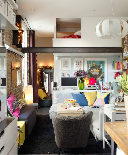 View of living room. Neutral coloured walls and sofa are brightened with colourful textiles, art work, books and storage