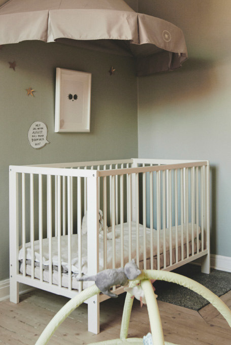Make a nursery sleeping area with a cot that converts to a bed under a cosy grey canopy decorated with golden stars