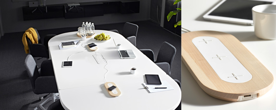 A conference table with two triple pads for wireless charging and a triple pad for wireless charging.