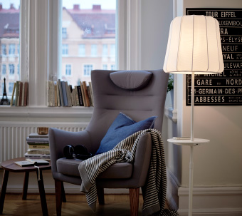 A floor lamp with wireless charging standing next to an armchair.