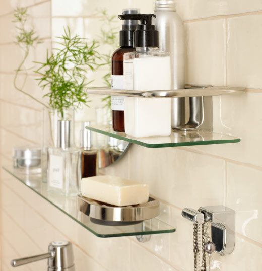 Glass shelves on a white tiled wall