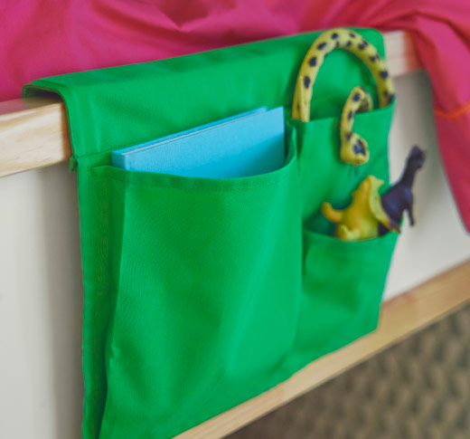 A green bed pocket filled with toys, hanging on the side of a bunk bed.
