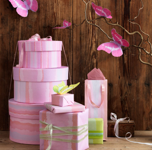 A display of pink gift boxes, gift wrap and butterfly decorations.