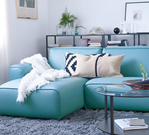 A living room with a two-seat sofa with chaise longue covered with a turquoise fabric that looks like leather.