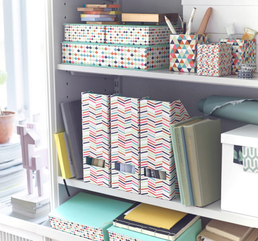A shelving unit filled with magazine files, box files and pen cups with colourful and geometric patterns.
