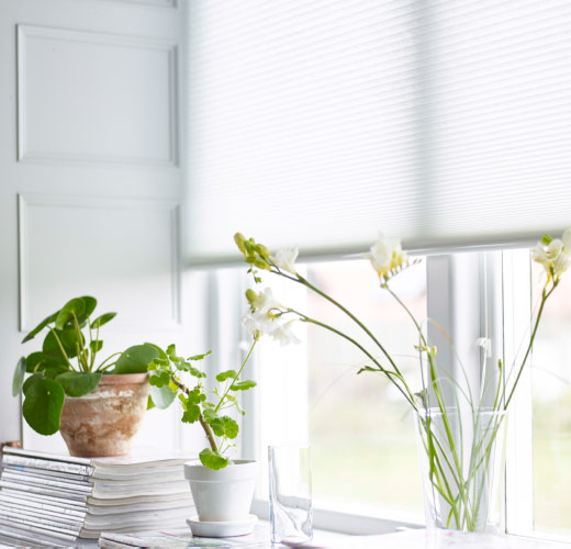 A window with a white cellular blind