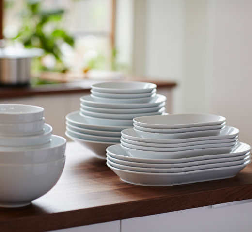 Stacked bowls and serving plates in white feldspar porcelain.