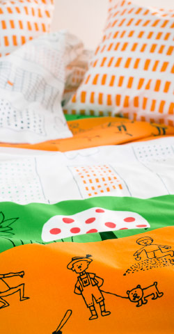 A close-up of a quilt cover and pillowcase in white, green and orange with a fun pattern of playing children.