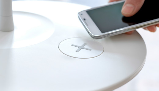 A close-up, showing how to charge your smart phone on a floor lamp with wireless charging.