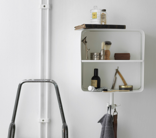 A white wall shelf in powder coated steel with a hook for towels underneath.