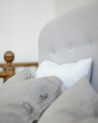 A close-up of a beige divan bed with a tufted and high headboard. Completed with bed linen in white, grey and beige.