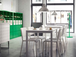 A café with white chairs and small tables together with green shelving units
