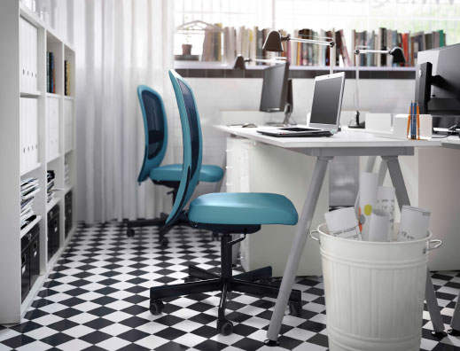 A small office with white desks, drawer units, shelf units and swivel chairs in turquoise