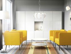 A modern conference room with yellow armchairs, a white round coffee table and white storage with some white doors