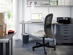 A small office with white desk, grey drawer unit and swivel chair also in grey