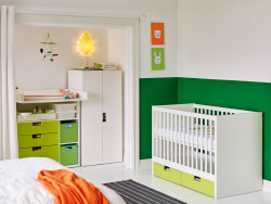 A bedroom with a white crib with green floor drawers combined with a white wardrobe and a white changing table with green drawers.