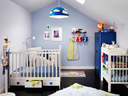 A nursery with a white cot with floor drawers and a changing table. Combined with a blue wardrobe.