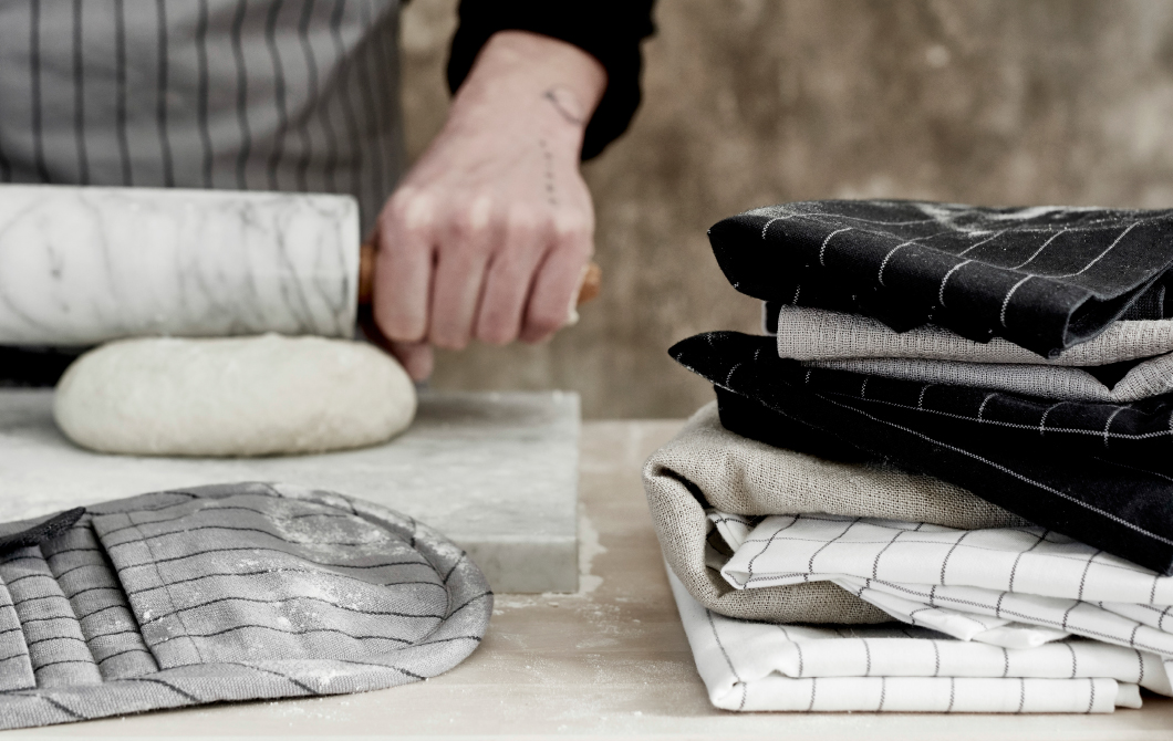 A close-up of a pastry board with pot holders, tea towels and aprons in black, grey and white.