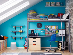 A teenage room with a silver-coloured loft bed with a desk and chest of drawers underneath.