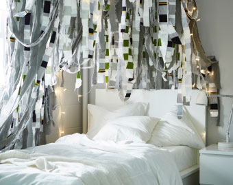 Cut fabric strips hanging from the ceiling above a bed