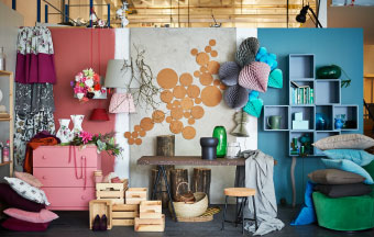 A display of pink chest of drawers, floral meter fabric, cork coasters and furniture, turquoise cushions and wall cabinets.""