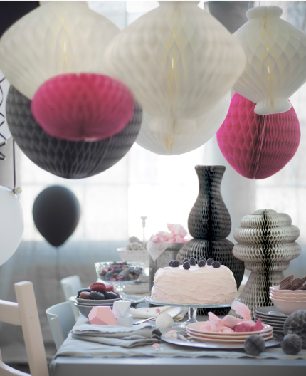 A dining table ready laid for a birthday party with hanging paper decorations in white, grey and pink.