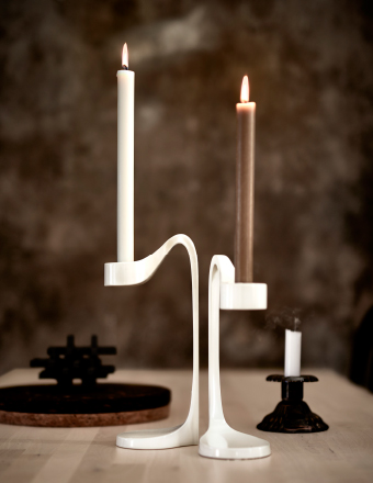 Two white candle holders with lit candles.