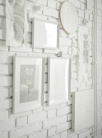 A white brick wall with white picture frames in different sizes.