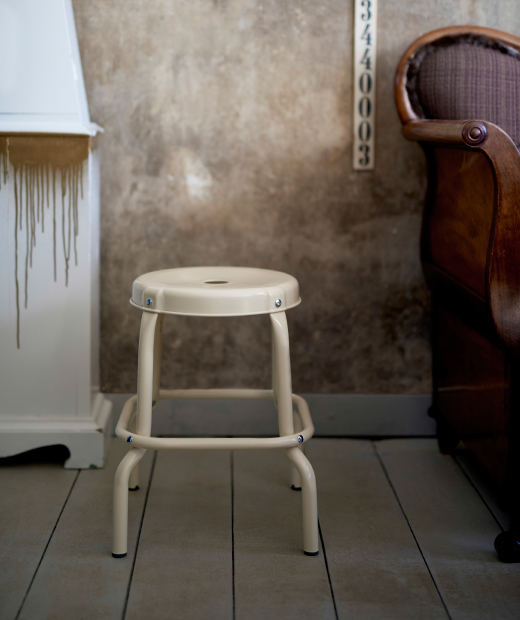 A close-up of a beige stool in powder coated steel.