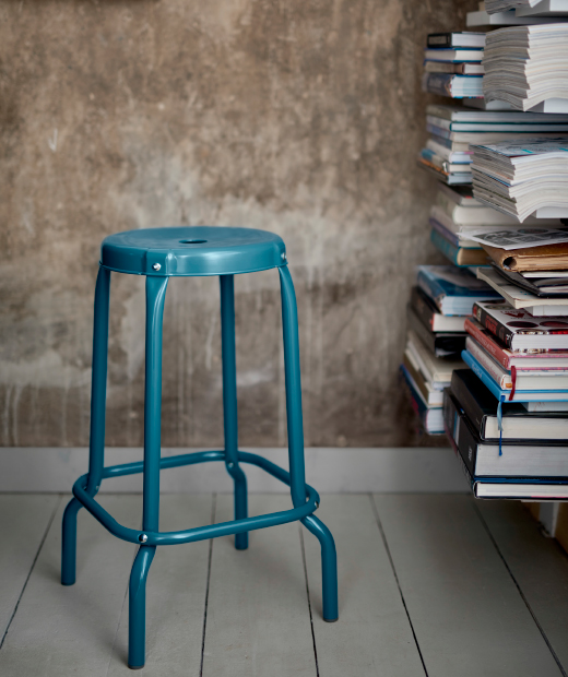 A close-up of a blue bar stool in powder coated steel.