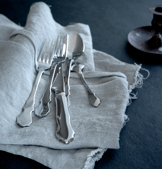 A close-up of a stainless steel cutlery set with a traditional shaped handle.