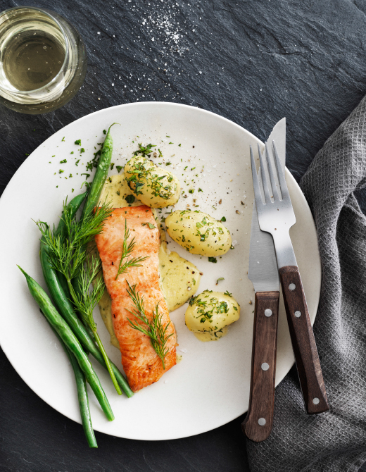 A white plate with one fried salmon fillet, boiled potatoes and green beans topped of with dill.