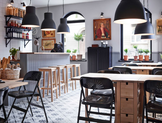 A restaurant with birch tables combined with chairs in black and birch bar stools.