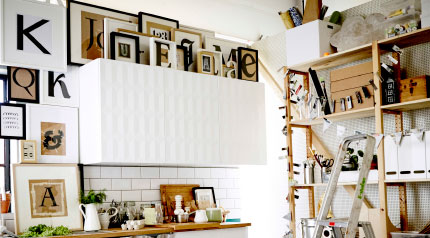 Frames with typography prints in black, white and beige surrounding a white kitchen wall cabinet