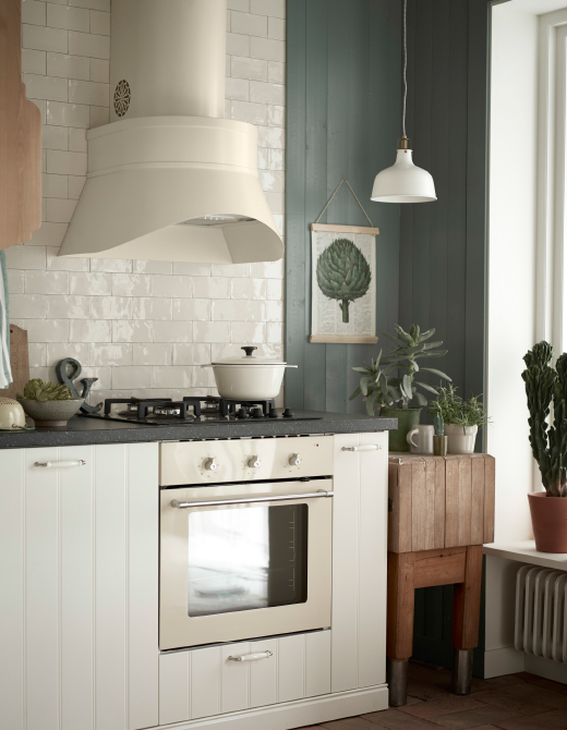 A white kitchen with a beige large extractor hood above a gas hob.