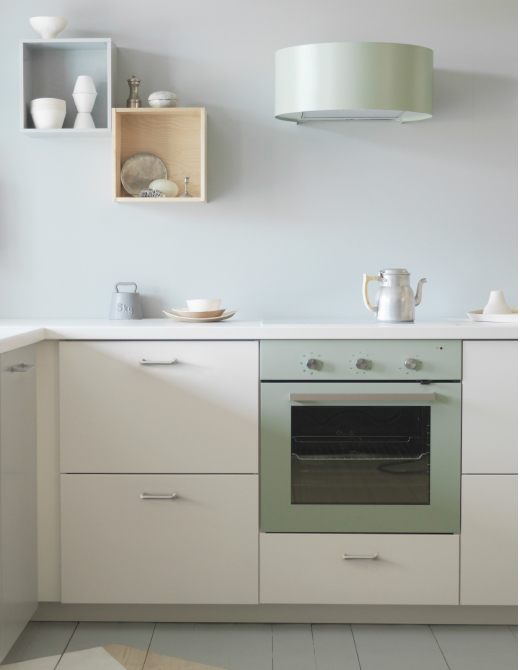 A white kitchen with a grey-green extractor hood above a glass ceramic hob.
