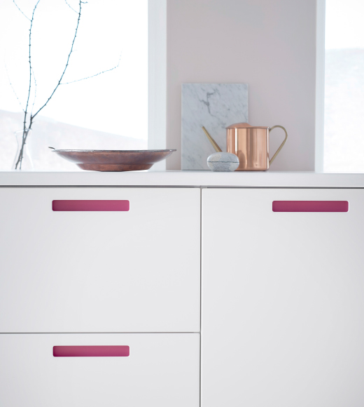 A close-up of a kitchen door with a pink handle that can be changed to oak, brown or white with a foil sticker that you attach to the inside of the handle.