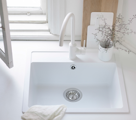 A close-up of a white single-bowl inset sink combined with a white single-lever kitchen mixer tap.