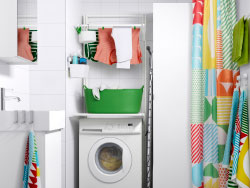 A white bathroom with washbasin cabinet and a high cabinet combined with towels and shower curtain in bright colours.
