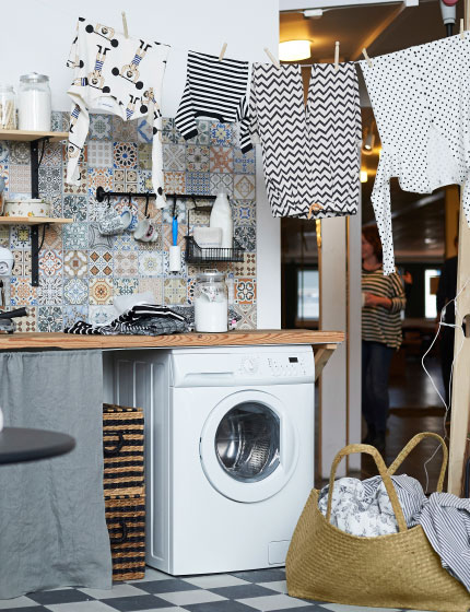 A laundry room with colorful tiles, hanging clothes, a laundry basket and a place to relax and read.