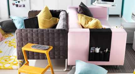 A grey and a pink sofa placed back-to-back in the center of a livingroom